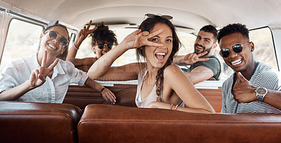 Buy stock photo Shot of a group of happy young friends making hand gestures while on a road trip together