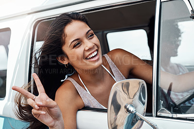 Buy stock photo Shot of a happy young woman making a v sign while enjoying a road trip