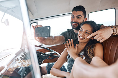 Buy stock photo Shot of a happy newly engaged young couple taking selfies on a road trip