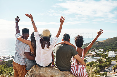 Buy stock photo Rearview shot of a group of friends sitting together on a rock overlooking the city