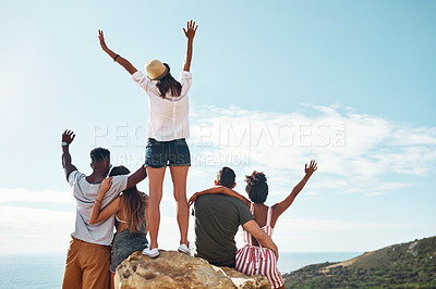 Buy stock photo Rearview shot of a group of friends looking cheerful at the top of a cliff