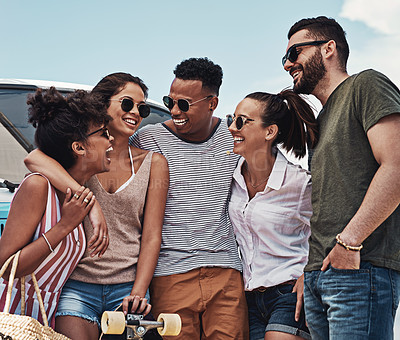 Buy stock photo Shot of a group of friends standing together while out on a road trip