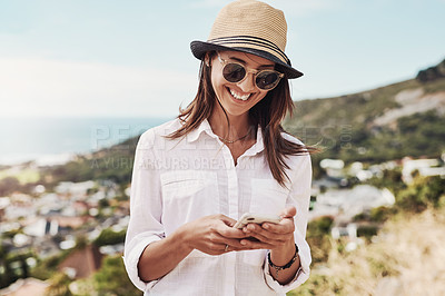 Buy stock photo Cropped shot of a young woman using her cellphone while standing outdoors