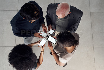 Buy stock photo High angle shot of a group of unrecognizable businesspeople using smartphones while standing together in a modern office