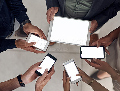 Buy stock photo High angle shot of a group of unrecognizable businesspeople using wireless technology while standing together in a modern office