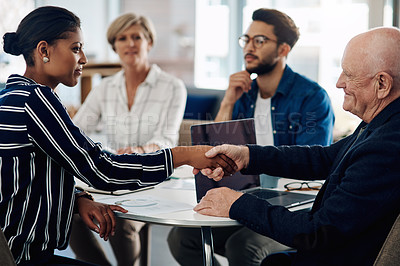 Buy stock photo Cropped shot of two businesspeople shaking hands during a meeting in a modern office