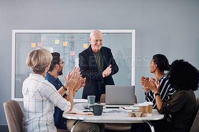 Buy stock photo Cropped shot of a handsome mature businessman receiving an applaud from his colleagues during a meeting in a modern office