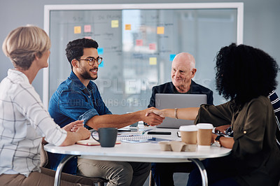 Buy stock photo Cropped shot of two young businesspeople shaking hands during a meeting in a modern office