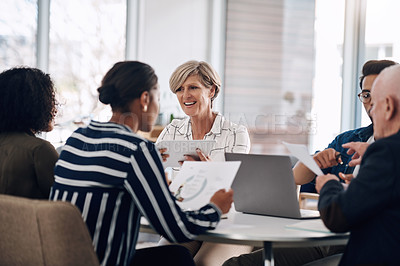 Buy stock photo Cropped shot of a diverse group of businesspeople using wireless technology during a meeting in a modern office