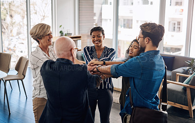 Buy stock photo Cropped shot of a diverse group of businesspeople joining their hands together in  a huddle while standing in a modern office