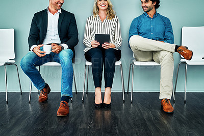 Buy stock photo Studio shot of a group of businesspeople using a digital tablet and chatting while waiting together against a blue background