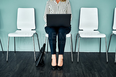 Buy stock photo Studio shot of a businesswoman using a laptop while waiting in line against a blue background
