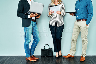 Buy stock photo Studio shot of a group of businesspeople having a discussion while waiting together against a blue background