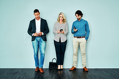 Buy stock photo Studio shot of a group of businesspeople using their smartphones while standing in line against a blue background