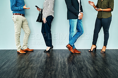 Buy stock photo Cropped studio shot of a group of businesspeople having a conversation while waiting together against a blue background