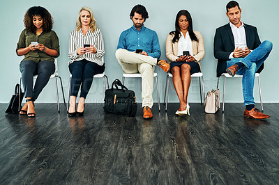 Buy stock photo Studio shot of a group of businesspeople using their smartphones while waiting in line against a blue background