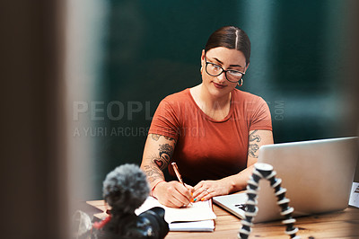 Buy stock photo Cropped shot of an attractive young businesswoman sitting alone at her desk and writing in her notebook