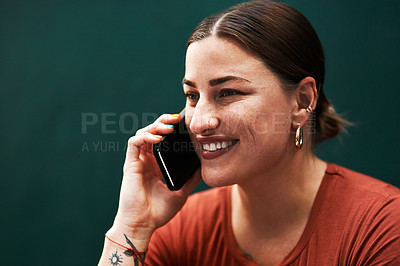 Buy stock photo Cropped shot of an attractive young businesswoman sitting alone against a green background and using her cellphone