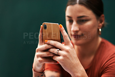 Buy stock photo Cropped shot of an attractive young businesswoman sitting alone against a green background and texting on her cellphone