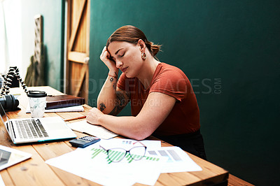 Buy stock photo Cropped shot of an attractive young businesswoman sitting alone at her desk and suffering from a headache