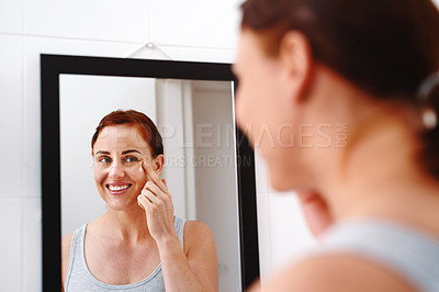 Buy stock photo Shot of an at attractive young woman applying moisturizer on her face in her bathroom at home