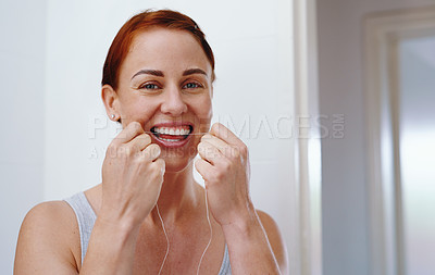 Buy stock photo Portrait of an attractive young woman flossing her teeth inside her bathroom at home