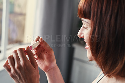 Buy stock photo Shot of an attractive young woman feeling happy while looking at her pregnancy test results at home