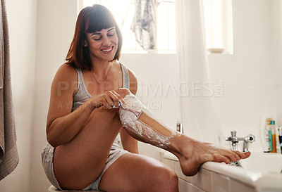 Buy stock photo Shot of an attractive young woman shaving her legs inside her bathroom at home