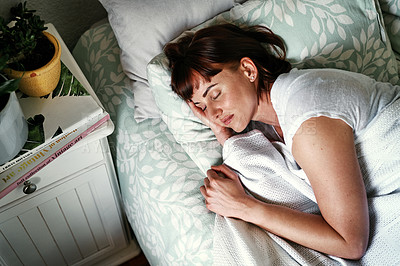 Buy stock photo High angle shot of an attractive young woman sleeping in her bed at home