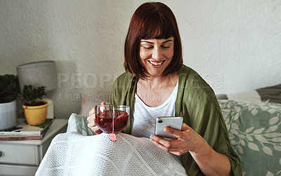 Buy stock photo Shot of an attractive young woman drinking tea and using her cellphone while relaxing in bed at home