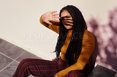 Buy stock photo Shot of a beautiful young woman sitting outside