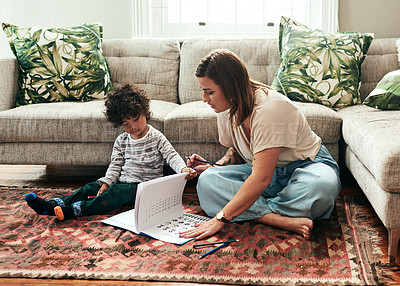 Buy stock photo Shot of a cheerful young woman and her son doing homework together while being seated on the floor in the living room