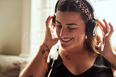 Buy stock photo Shot of a young woman using headphones on the sofa at home