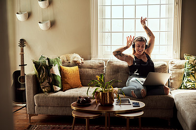 Buy stock photo Shot of a young woman using a laptop and headphones on the sofa at home