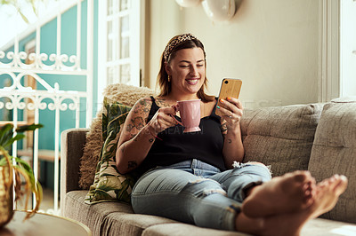 Buy stock photo Shot of a young woman having coffee and using a smartphone on the sofa at home