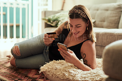 Buy stock photo Shot of a young woman using a smartphone and credit card in her living room at home