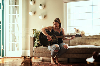 Buy stock photo Shot of a young woman playing a guitar on a relaxing day at home