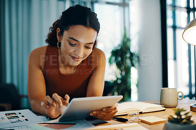 Buy stock photo Cropped shot of a young designer using a digital tablet  at her desk