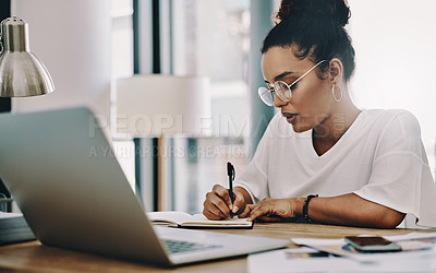 Buy stock photo Shot of a young businesswoman writing in a notebook while working in her home office