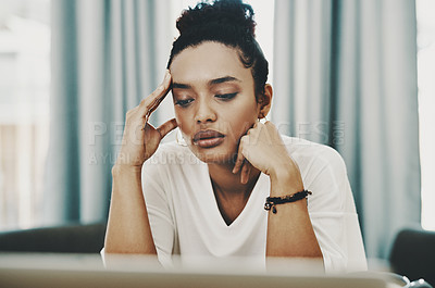 Buy stock photo Shot of a young businesswoman looking stressed while using a laptop in her home office