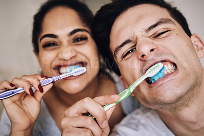 Buy stock photo Cropped shot of a young couple brushing their teeth together