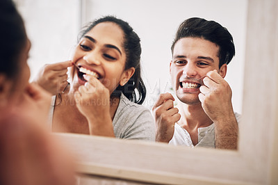 Buy stock photo Cropped shot of a young couple flossing their teeth together