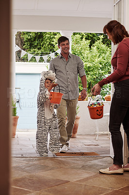 Buy stock photo Full length shot of an adorable little boy trick or treating with his father on halloween