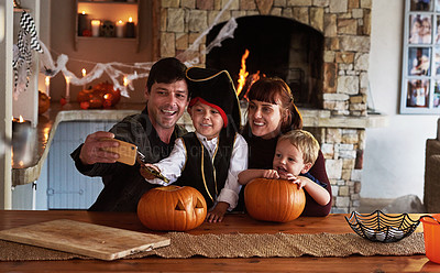 Buy stock photo Shot of an adorable young family taking selfies together with a cellphone on halloween at home