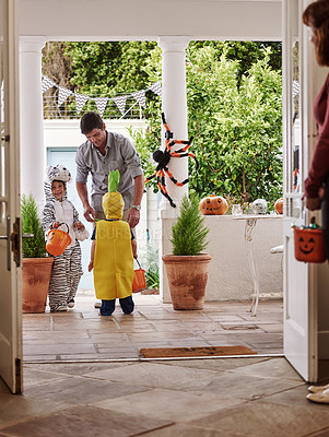 Buy stock photo Full length shot of two adorable little boys celebrating halloween with their parents at home