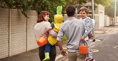 Buy stock photo Rearview shot of an adorable young family trick or treating together in the neighborhood on halloween