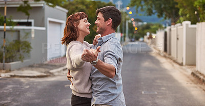 Buy stock photo Shot of an affectionate young couple dancing together on the street