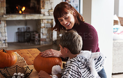 Buy stock photo Shot of a happy young mother carving out pumpkins and celebrating halloween with her young son at home