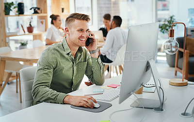 Buy stock photo Cropped shot of a handsome young businessman sitting and using his cellphone while using his computer in the office