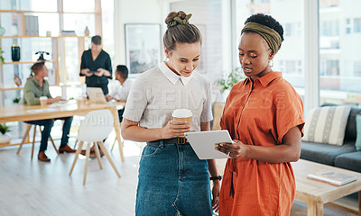 Buy stock photo Cropped shot of two attractive young businesswomen standing together and having a discussion in the office